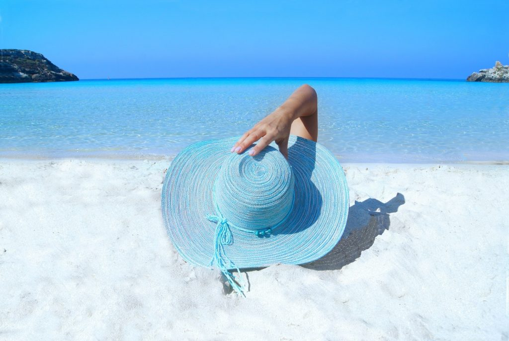 woman blue hat beach ocean sunbathing vacation