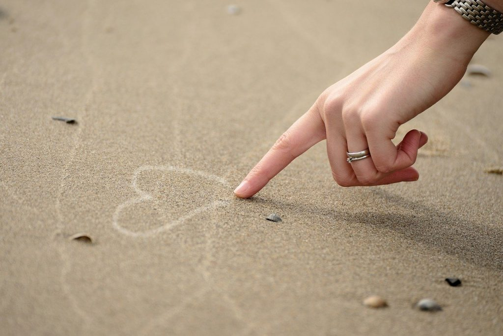 woman hand drawing heart in sand